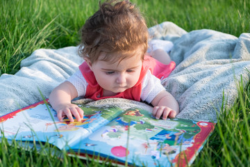 Little girl (six months old) reads a large book with pictures. She lies on the grass in the park.