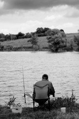 Fisherman on river. Man in folding chair on river bank expects fish. Landscape with storm clouds. Black and white photo.