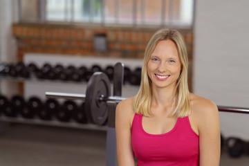 attraktive blonde frau sitzt im sportstudio auf einer hantelbank