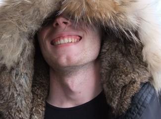 Небритый мужчина в меховом капюшоне.