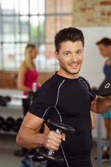 sportler trainiert im fitnessstudio mit kurzhanteln