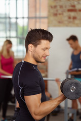 sportlicher mann trainiert die arme im fitness-club