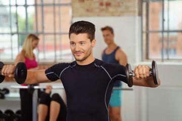 mann trainiert die oberarme im fitness-center mit kurzhanteln