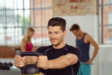 bodybuilder trainiert mit kettleball im studio