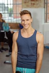 lächelnder sportlicher mann im fitnessstudio