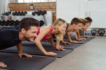 gruppe macht liegestütz in einem fitness-kurs im studio