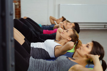 gruppe trainiert die bauchmuskulatur im fitness-studio