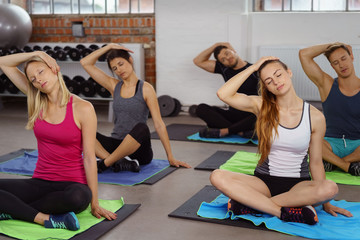 gruppe im fitnessstudio dehnt die nackenmuskulatur