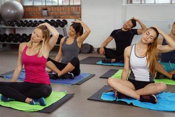 gruppe im fitnessstudio sitzt auf matten und dehnt die muskulatur