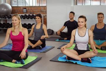 sportliche gruppe sitzt im schneidersitz auf dem boden im fitnessstudio