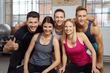 lachendes team im fitnessstudio zeigt daumen hoch