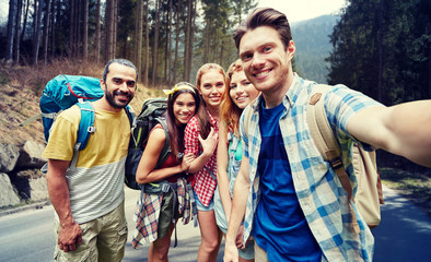 friends with backpack taking selfie in wood