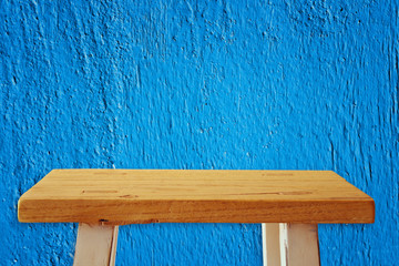 Empty small table in front of blue wall background