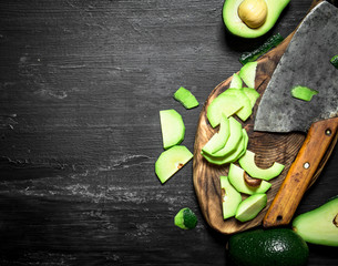 Sliced avocado with a hatchet on the Board.