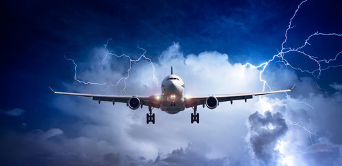 Passenger airplane flying above sea on stormy sky with dark clouds and lightnings.
