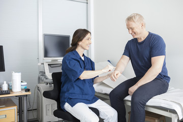 Smiling Doctor Touching Male Patient's Hand In Clinic