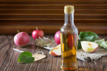 Apple cider vinegar in a glass bottle with fresh apples on a tab
