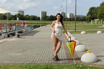 Piękna kobieta w porcie z parasolką i tatuażem.