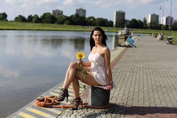 Piękna kobieta siedzi nad brzegiem rzeki.