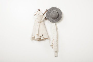 Clothes and hat hanging from hooks on white wall