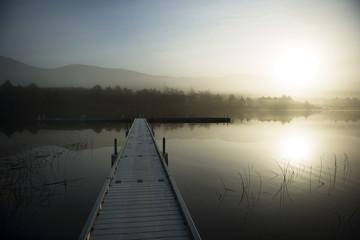 Pier over lake against sky at sunrise