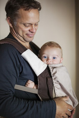 Father carrying baby in carrier against the wall
