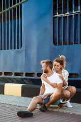 Young beautiful couple walking around city, smiling, sitting on skates.