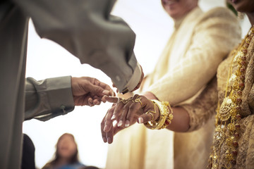 Low angle view of priest tying fingers of bride and groom