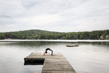 Woman exercising on pier over lake against sky