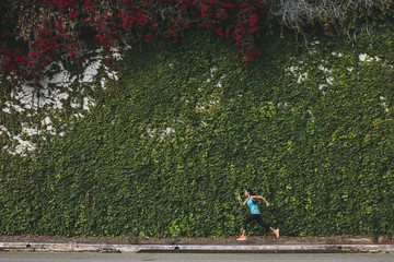 Side view of woman running against ivy covered wall