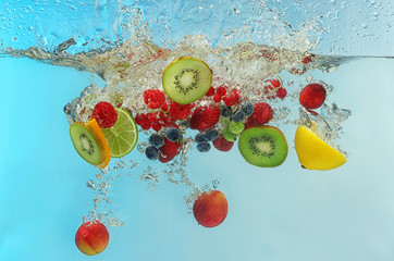 Berries and fruits falling into water on color background