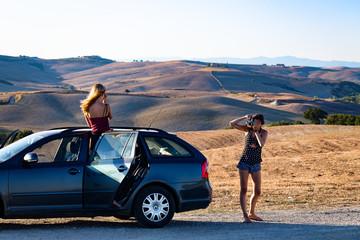 deux jeunes filles, sur le bord de la route et dans une voiture font des photos devant un paysage de Toscane en Italie