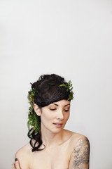 Sensuous young woman wearing leaves in hair against white background
