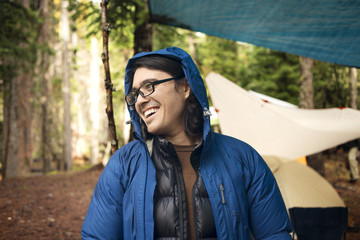 Happy man looking away at campsite in forest