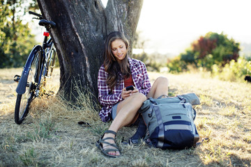 Young woman using mobile phone while sitting with backpack and bicycle on grassy field