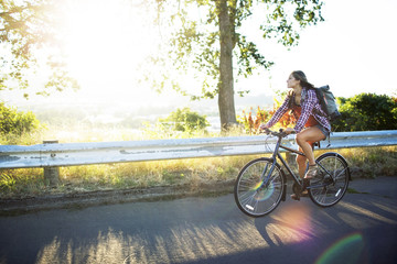 Young woman riding bicycle on road during summer
