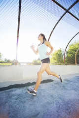 Young woman running against fence