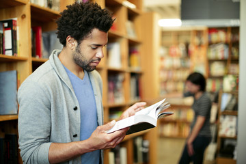 Man reading book in library with woman standing in background