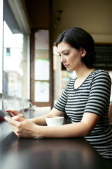 Serious young woman using digital tablet at cafe table