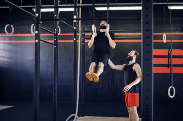 Trainer assisting athlete in exercising on gymnastic rings
