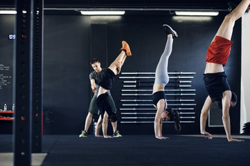 Trainer assisting athlete in doing handstand at gym