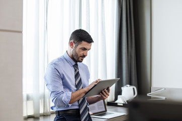 Businessman using tablet computer while standing by window in hotel room