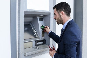Side view of businessman using ATM at subway station