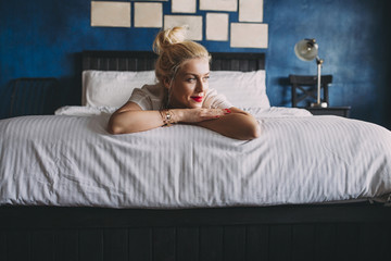 Smiling woman relaxing on bed at home Wall mural
