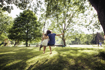 Rear view of sisters sitting on swing at grass field
