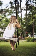 Rear view of girl sitting on swing at park