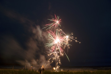 Low angle view of fireworks at beach against sky at night