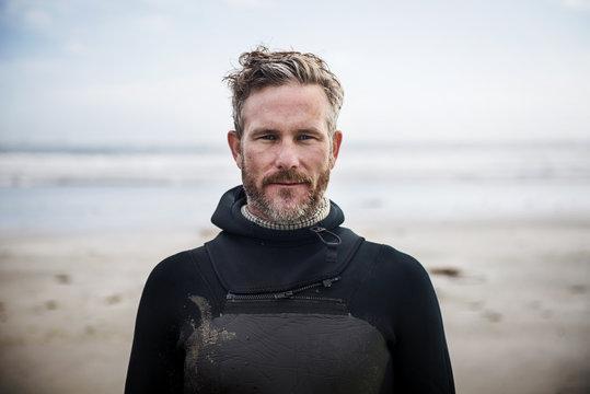 Portrait of confident surfer standing at beach