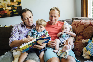Gay couple reading book with sons on sofa at home