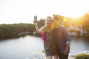 Friends taking selfie through smartphone by lake during sunset